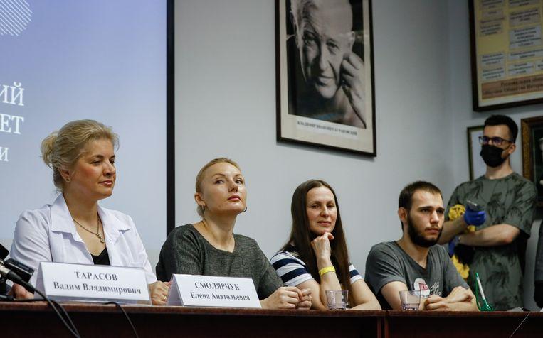 Onderzoeker Elena Smolyarchuk (links) tijdens een persconferentie. Naast haar vrijwilligers die hebben deelgenomen aan het onderzoek naar een coronavaccin. Beeld EPA
