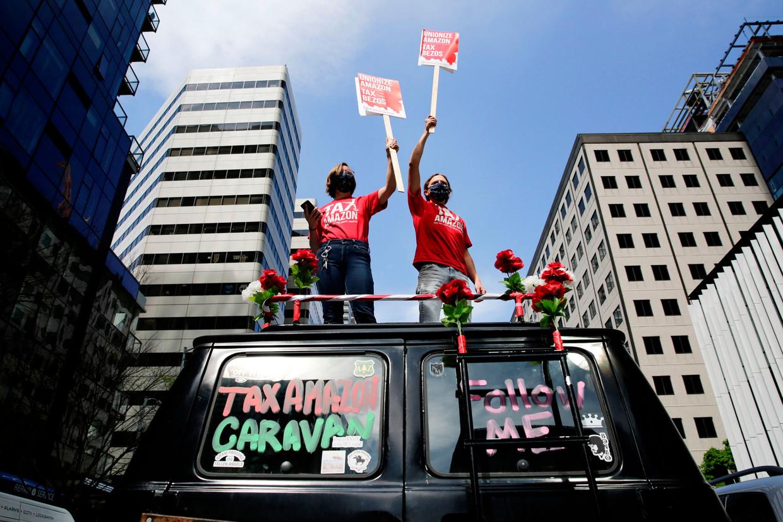 Op 1 mei reden mensen in Seattle rond in een karavaan om te protesteren tegen Jeff Bezos, de grote baas van Amazon. '24 miljard dollar winst sinds Covid-19', staat op het bord.  Beeld AFP