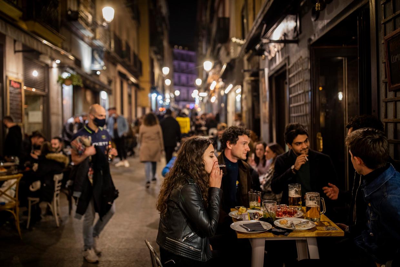 Toeristen genieten van een etentje buiten in Madrid. Beeld AP
