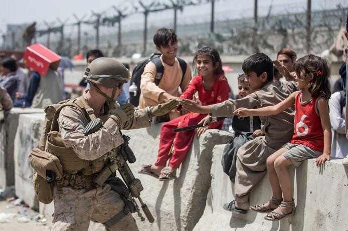 Een Amerikaanse marinier dolt even met enkele Afghaanse kinderen te midden van de chaos op de luchthaven van Kaboel.