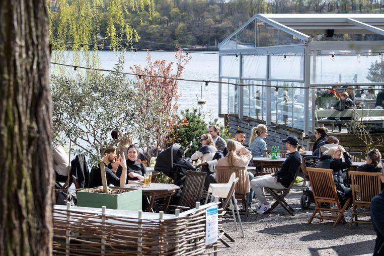 Zweden genieten van een terrasje aan het water. Ondanks de soepele maatregelen had het Scandinavische land geen economische winst tijdens de coronaperiode. Beeld EPA