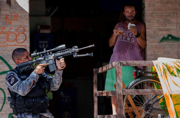 In de beruchte Rocinha-favela in het zuiden van de Braziliaanse stad Rio de Janeiro patrouilleert een lid van de militaire politie met schietklaar mitrailleur op de schouder. De lokale bewoner lijkt meer verrast door de fotograaf. Foto Mauro Pimentel