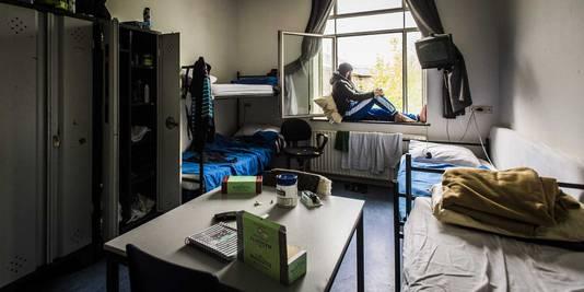 Een bewoner uit Syrie zit in het raamkozijn van zijn kamer in het asielzoekerscentrum in Utrecht