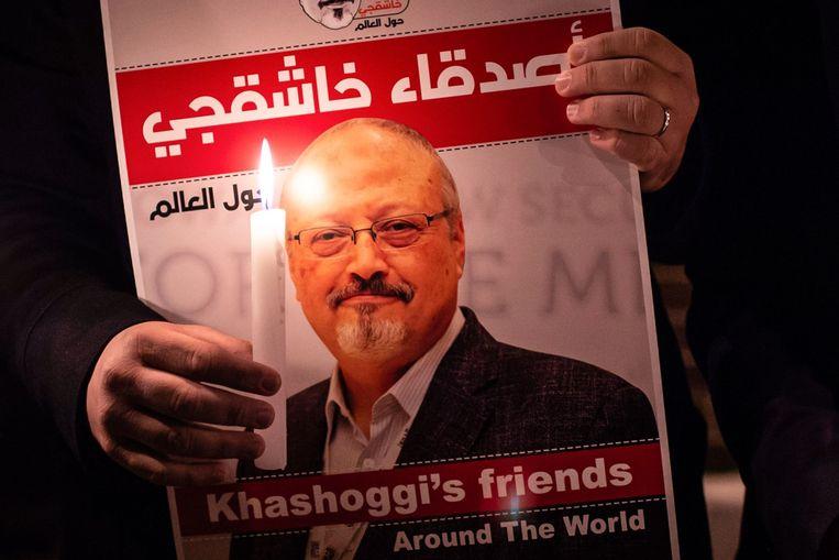 Een foto van Khashoggi die een demonstrant vasthoudt, samen met een kaars. Beeld AFP