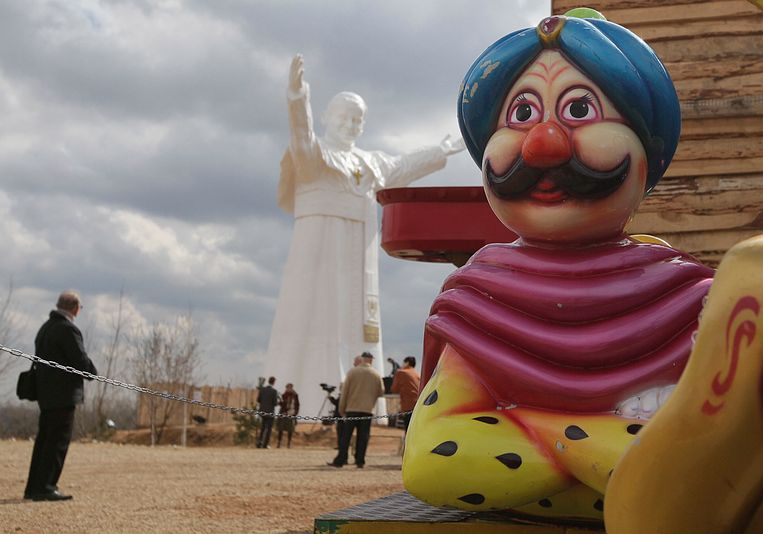 A children's playground statue is seen in the foreground as residents attend the unveiling ceremony of the statue of the late Pope John Paul II in Czestochowa, Poland, on Saturday, April 13, 2013. Archbishop Waclaw Depo unveiled the 13.8-meter (45.3-foot) white fiberglass figure that was funded by a businessman, Leszek Lyson, in gratitude for what he believes was an intervention by the late pontiff in saving his drowning son. (AP Photo/Czarek Sokolowski) Beeld AP