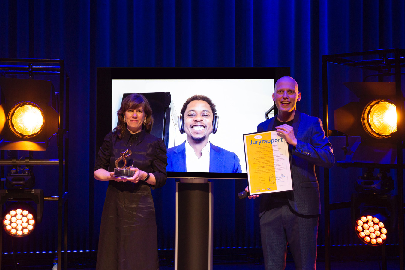 Typhoon (midden) was niet live aanwezig bij de prijsuitreiking. Anneke Dorsman (links) nam namens Het Klokhuis de prijs in ontvangst.