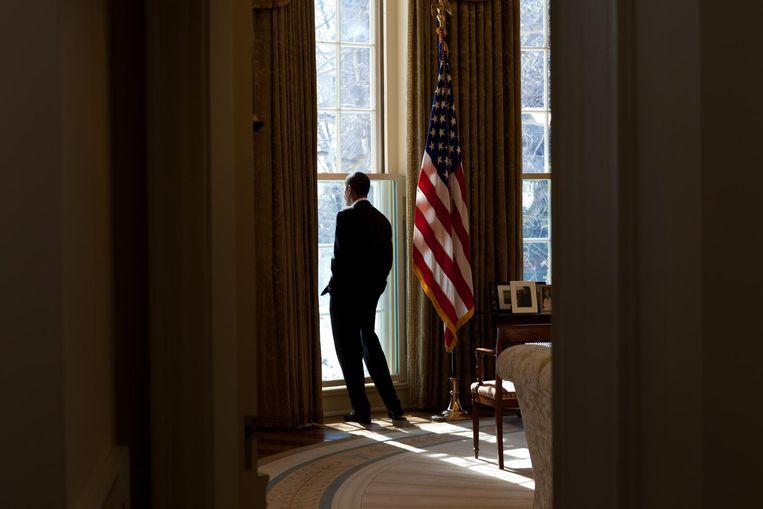 Obama werpt een blik uit het raam van de Oval Office. Beeld Pete Souza / The White House