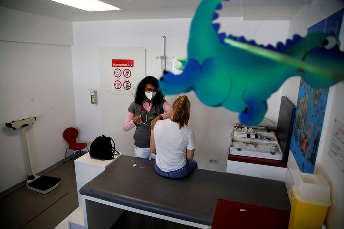 Een arts zet een coronaprik bij een tiener in het Duitse Bonn. Het BioNTech/Pfizer-vaccin is goedgekeurd voor kinderen maar pas vanaf 12 jaar. Foto ter illustratie, dit is niet de beschreven arts.