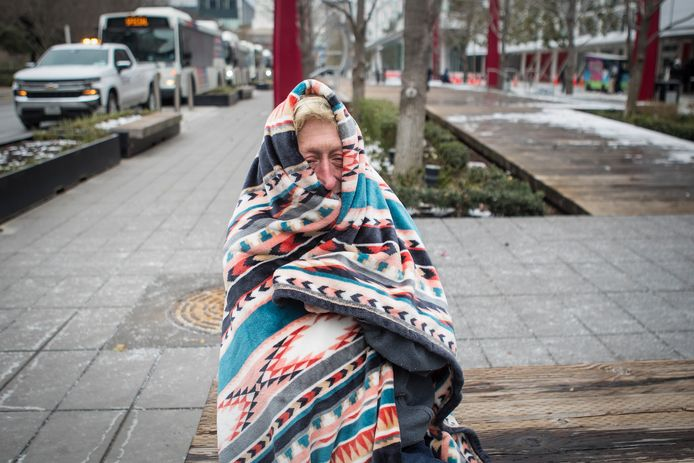 Een vrouw probeert zich in Houston, Texas warm te houden met een deken.