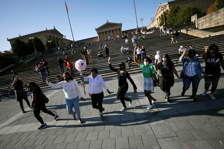 Leden en oud-leden van het eerste zwarte damesdispuut van het land, Alpha Kappa Alpha, dansen in Philadelphia omdat hun oud-lid Kamala Harris de nieuwe vice-president wordt. Beeld AP