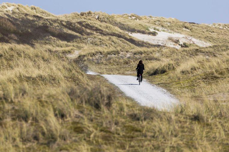 Een eenzame fietser in de duinen op Ameland. De gemeente ziet inkomsten uit toeristenbelasting verdampen. Beeld ANP
