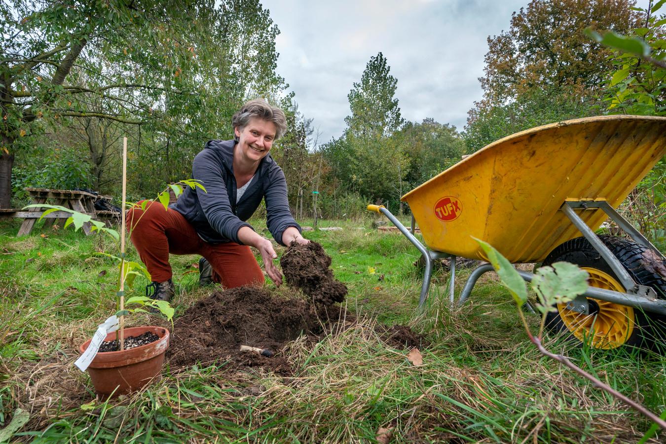 Marianne Galema met haar handen in de aarde met het planten in het voedselbos in Boxtel.