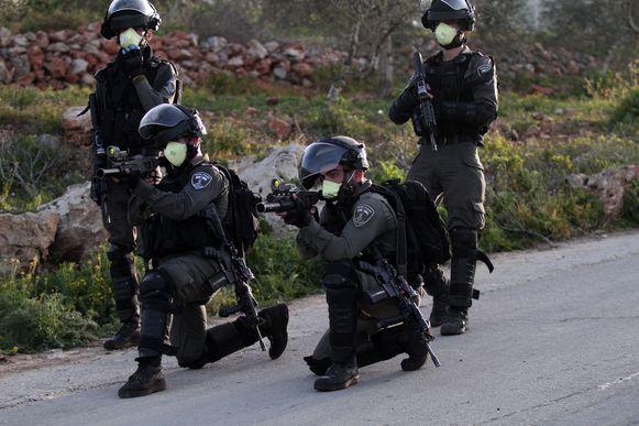 Israëlische soldaten richten hun wapens op Palestijnse betogers.