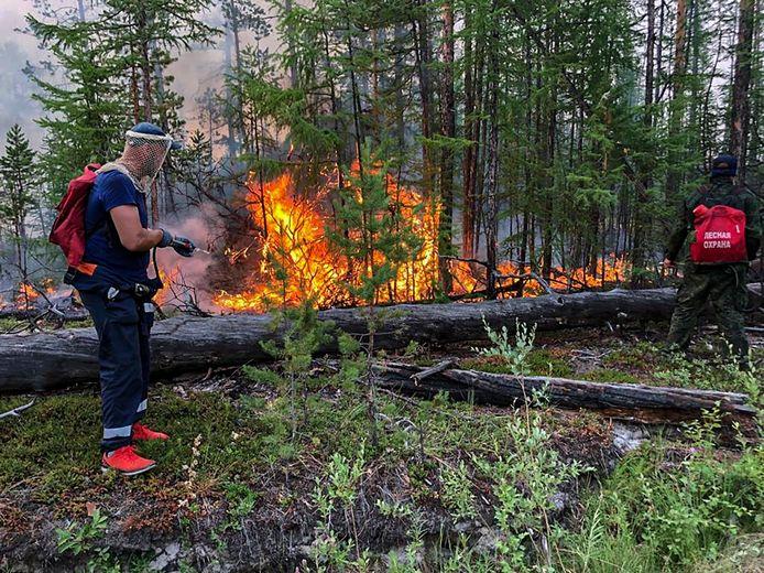 Een brandweerman probeert het vuur in Jakoetië te bestrijden.