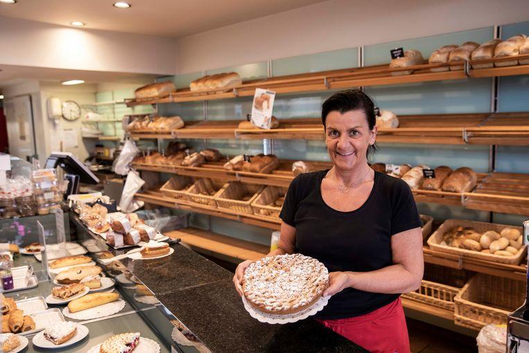 Ingrid, die in één van de 23 winkels van  Vangrootloon werkt toont fier haar Limburgse Vlaai.