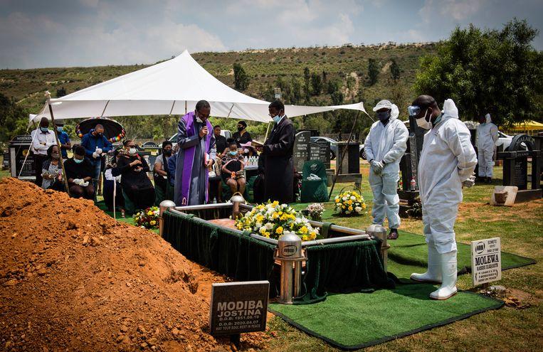Thabang Mpina (rechts), volledig ingepakt in beschermende kleding, luistert samen met de familie van de overledene naar het gebed van de predikant.  Beeld Bram Lammers