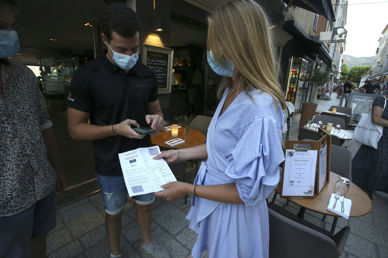 Een restauranthouder checkt de vaccinatiebewijzen van twee toeristen op Corsica.