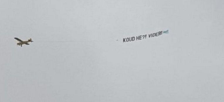 Het vliegtuigje dat boven het Museumplein cirkelde met de tekst 'Koud he?! Videre'. Beeld Videre