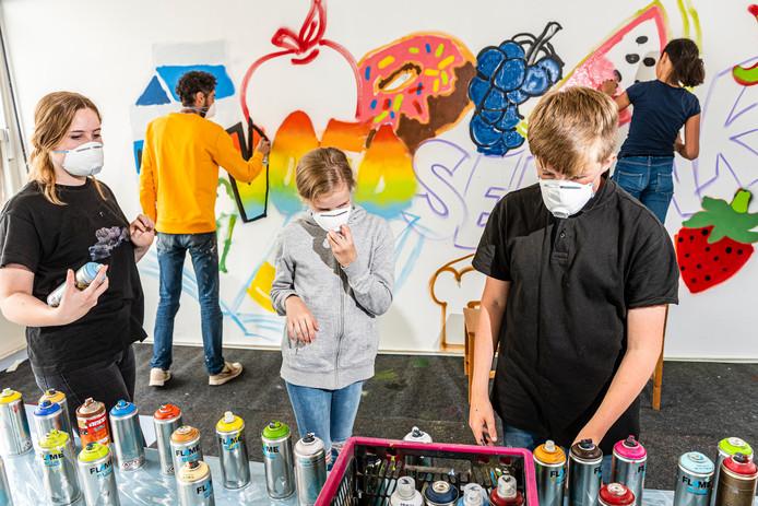 De Voedselbank krijgt een muurschildering van het Scala College. Leerlingen Sanna (rechts), Bas, Naomi (links) en Ymke (midden) werken onder begeleiding van kunstenaar Joost zwanenburg.