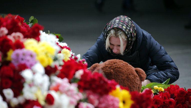 Een vrouw legt bloemen neer bij een vliegveld in Sint Petersburg Beeld ANP