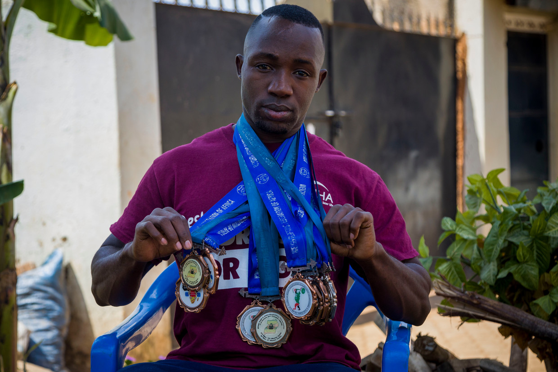 Julius Ssekitoleko toont in Kampala de medailles die hij won met gewichtheffen en daarvoor rugbyen en waar hij zo graag een olympische plak aan had toegevoegd. Beeld Katumba Badru Sultan