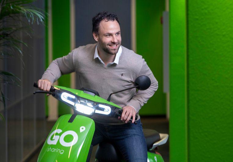 Raymon Pouwels, CEO van Go Sharing op een van zijn appelgroene deelscooters.  Beeld Werry Crone