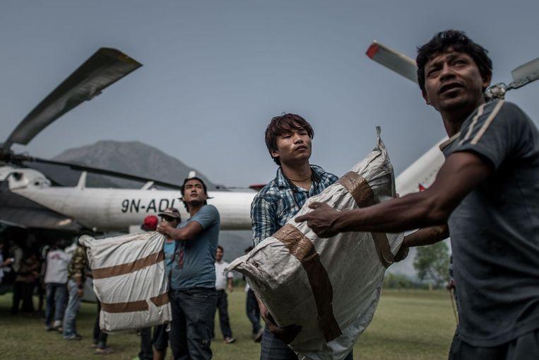 Mensen laden hulpproducten uit een helikopter van het Wereldvoedselprogramma in het dorp Deurali. Beeld afp