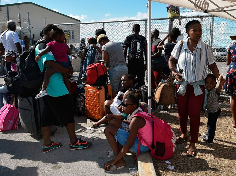 Mensen staan in de rij bij de luchthaven van Freeport op Grand Bahama Island om naar de VS te vliegen. Beeld AFP