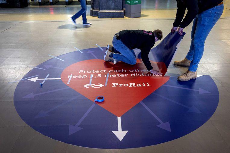 Een sticker op de vloer van station Amsterdam CS. Via de stickers herinnert de NS de reizigers eraan voldoende afstand tot elkaar te nemen, om verdere verspreiding van het coronavirus te voorkomen. Beeld ANP