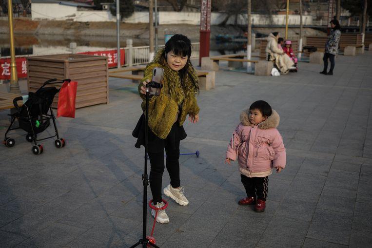 Ook in China zijn het vooral de moeders die voor de kinderen zorgen.  Beeld EPA