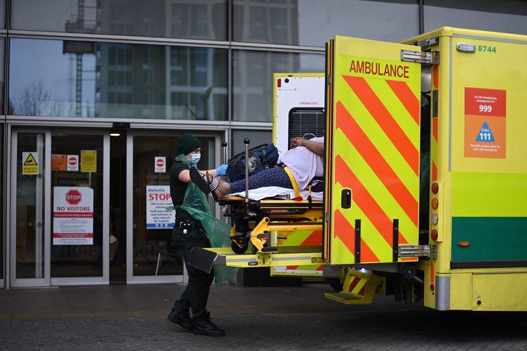 Een ambulancemedewerker helpt een patiënt het Royal London-ziekenhuis in. Beeld AFP