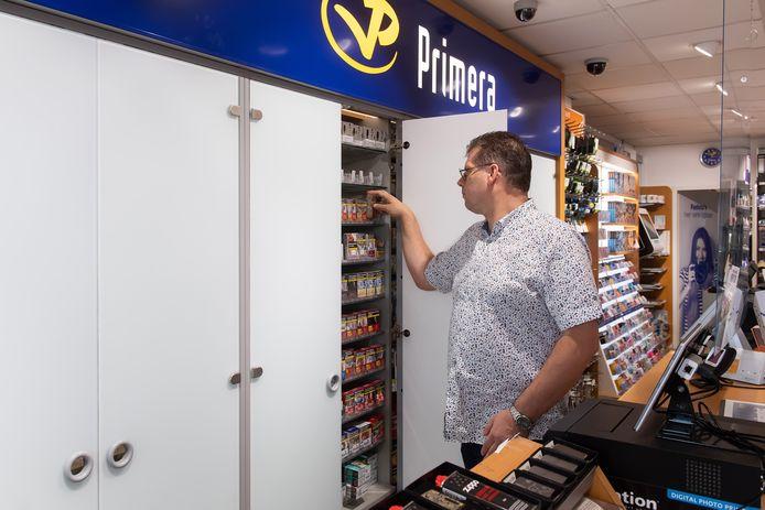 Ronald Nagtzaam pakt een pakje sigaretten uit de kast die ondoorzichtige deuren hebben.