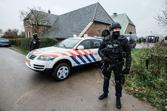 Zwaarbewapende agenten bewaken de boerderij in het buitengebied tussen baak en Toldijk, waar zondag een drugslab in opbouw werd gevonden.