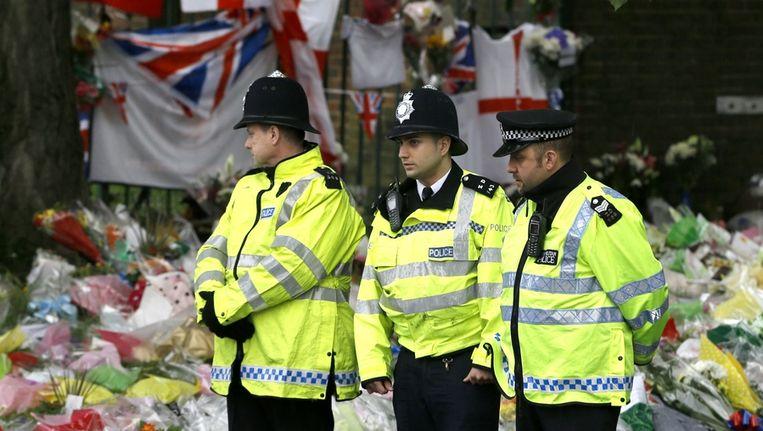 Britse agenten bij de duizenden bloemen op de plaats waar de militair Lee Rigby werd vermoord. Beeld ap