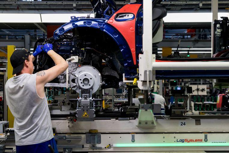 Een medewerker bij een assemblagelijn van Mini's bij autofabrikant VDL Nedcar in Born. De productie komt deze week opnieuw stil te liggen doordat er een onderdeel ontbreekt. Beeld ANP