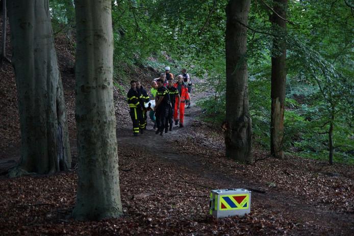 Hulpverleners dragen de gewonde door het bos.