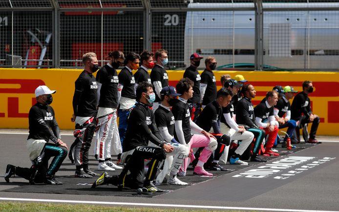 Kevin Magnussen (staand vooraan) voegde zich bij het rijtje coureurs dat niet knielde voor de start van de Grand Prix van Groot-Brittannië.