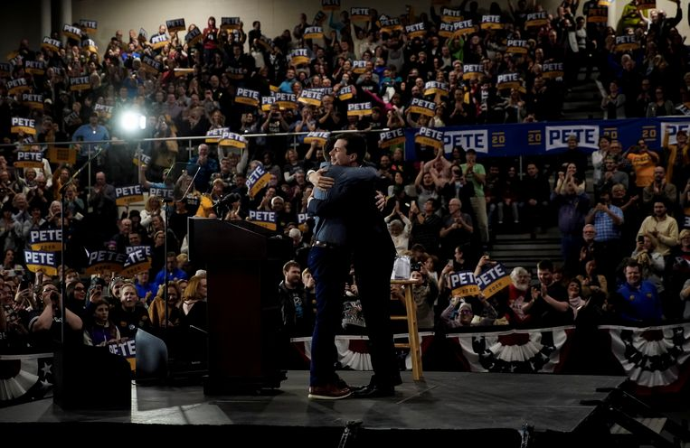 Buttigieg omhelst zijn man Chasten op het podium in Raleigh, North Carolina.  Beeld REUTERS