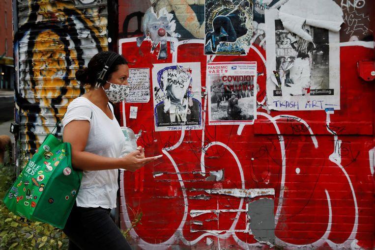 Een vrouw met mondmasker naast graffiti in Brooklyn, New York. Beeld REUTERS