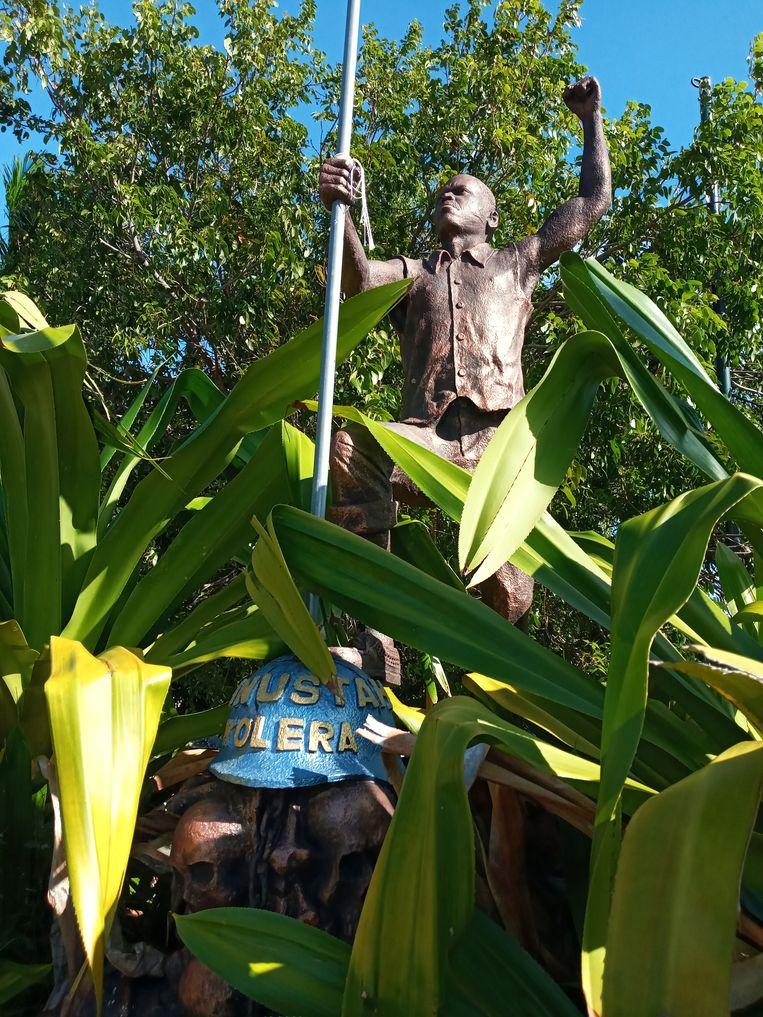 Een standbeeld in Port-Salut beeldt het Minustah-leed uit. Op de blauwe helm staat 'Minustah Kolera'. Beeld foto Joost de Vries