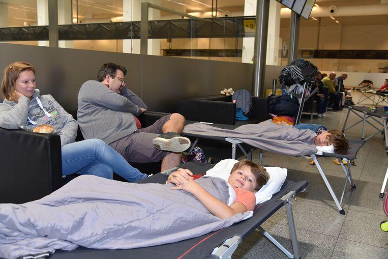 Gaëlle, Jean-Philippe en hun zoons Baptiste (10) en Clément (12) moesten 19 uur wachten tot ze met een bus naar Amsterdam werden gebracht voor een andere vlucht naar Antalya. Beeld Dieter Nijs