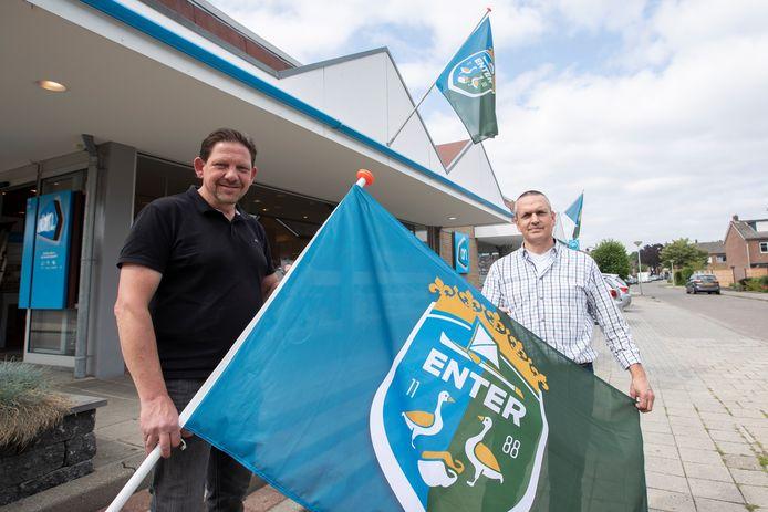Initiatiefnemers Eric Tijhof (links) en Patrick ten Hove achter een vlag met het Enterse dorps wapen.