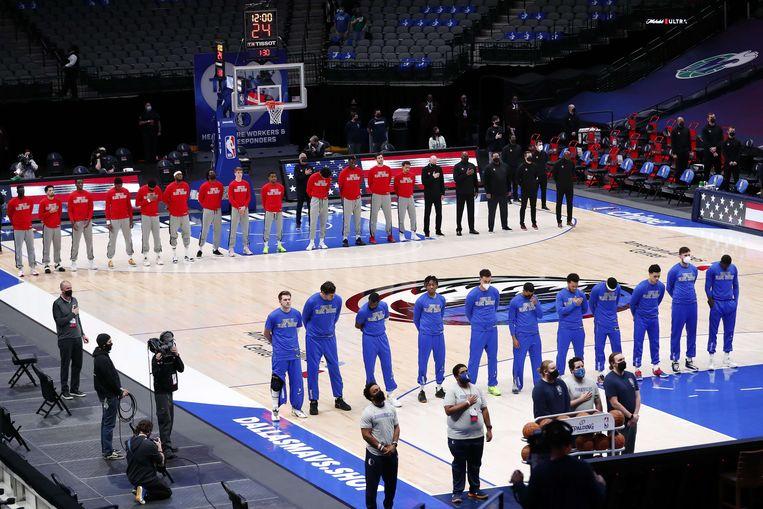 De Dallas Mavericks en de Atlanta Hawks luisteren woensdag naar het teruggekeerde volkslied. Beeld AFP
