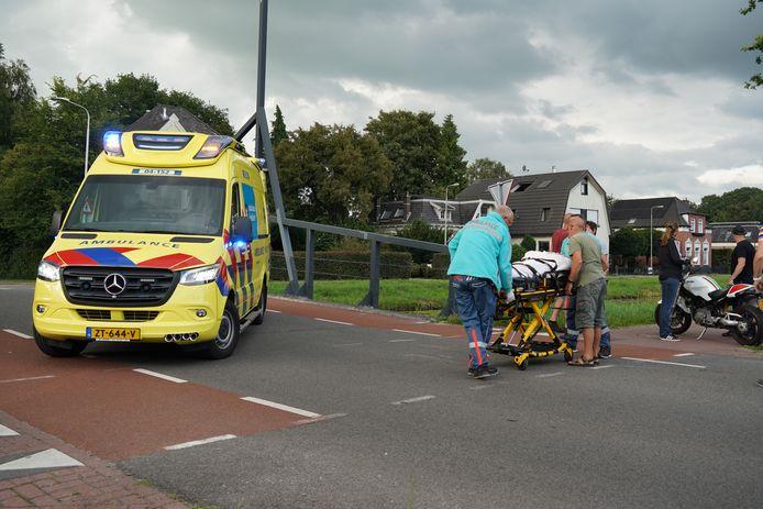 Het ambulancepersoneel is bezig om het slachtoffer de ambulance in te rijden.
