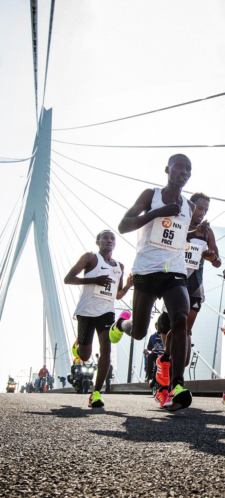 Uiterst links loopt Abdi Nageeye bij het 27 kilometerpunt op de Erasmusbrug. Beeld Jiri Buller / de Volkskrant