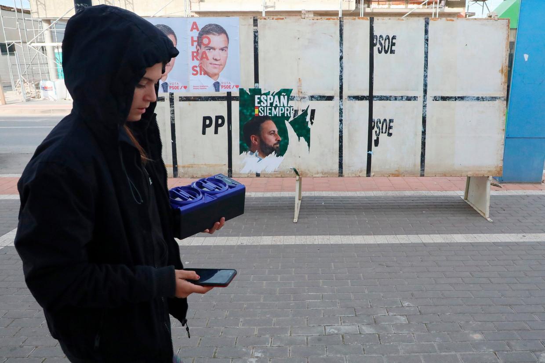 Een meisje loopt voorbij een verkiezingsposter van Vox.  Beeld AP