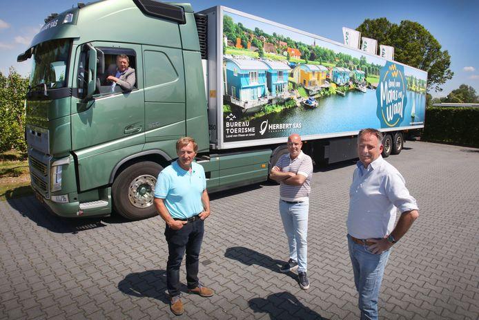 Wethouder René Cruijsen achter het stuur van de truck van SAS Transport & Fruit. Voor de trailer met reclame voor het Land van Maas en Waal ondernemers Adri van Ooijen en Herbert Sas en directeur van Bureau Toerisme Richard de Bruin (vlnr).