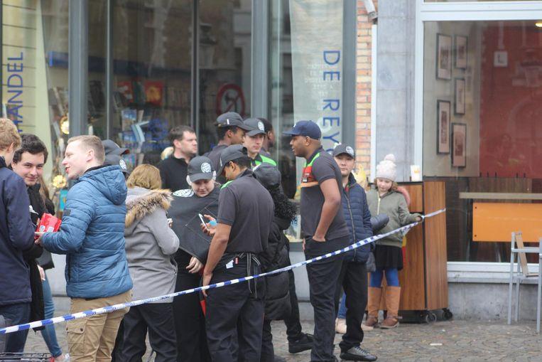 Klanten en personeel van het hamburgerrestaurant wachten achter het politielint tot ze opnieuw naar binnen mogen.