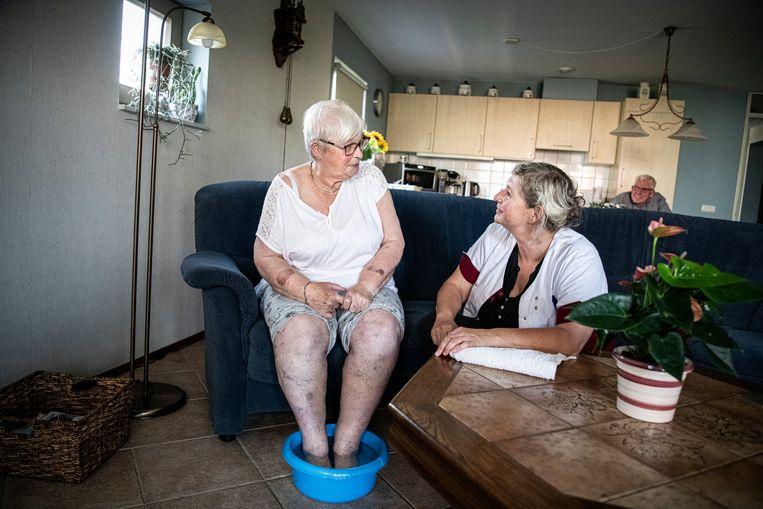De thuishulp helpt een wat oudere mevrouw met een voetenbadje.  Beeld Koen Verheijden