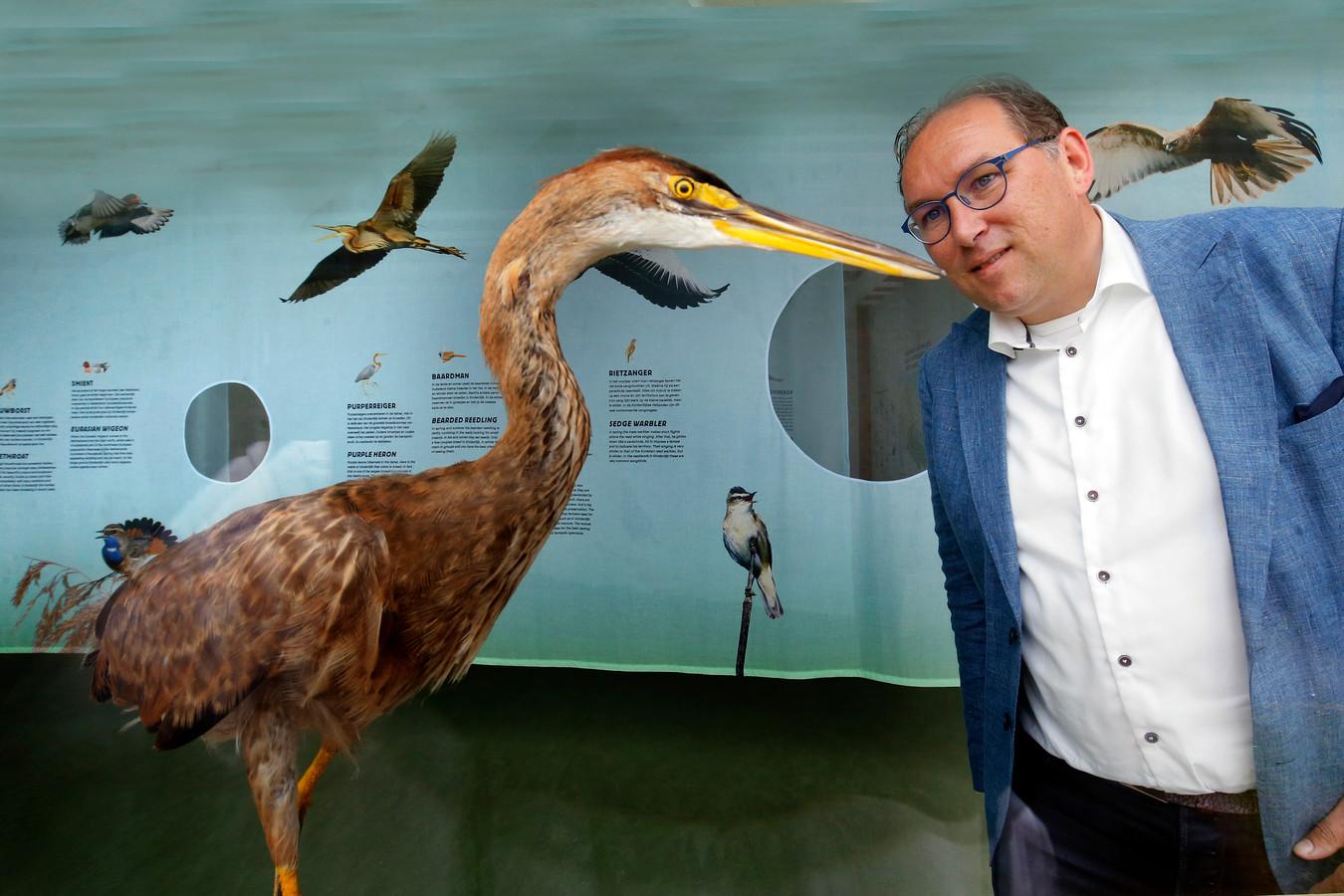 Directeur-bestuurder Peter-Jan van Steenbergen kijkt naar een opgezette purperreiger die in het Vogeltheater bij Kinderdijk poseert. Op de achtergrond staat allemaal informatie over de vogels die in het gebied voorkomen.
